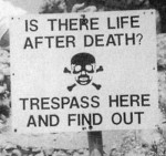 """Sign Reading """"Is There Life After Death? Trespass Here and Find Out."""""""