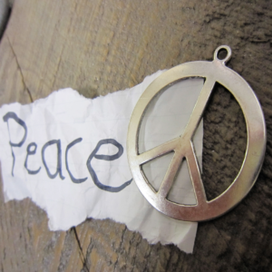photo of peace symbol and torn sheet of paper with word peace on it